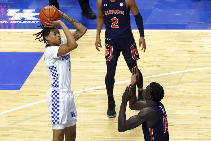 Kentucky's B.J. Boston, left, shoots over Auburn's JT Thor during the second half of an NCAA college basketball game in Lexington, Ky., Saturday, Feb. 13, 2021. (AP Photo/James Crisp)