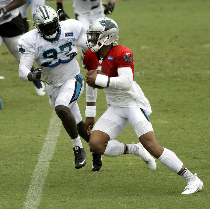 File-This July30, 2018, file photo shows Carolina Panthers' Cam Newton, right, running the ball as Mario Addison, left, pursues during an NFL football practice at the team's training camp in Spartanburg, S.C. Addison has spent his entire life shedding labels. Now the former undrafted rookie from Troy who was waived by three other NFL teams appears on the verge of joining the upper echelon of the league's defensive ends entering his eighth season. The 30-year-old Addison has slowly but steadily worked his way up through the NFL ranks, going from being a special teams player early in his career to a third-down pass rush specialist and finally to an every down defensive end last season.  (AP Photo/Chuck Burton, File)