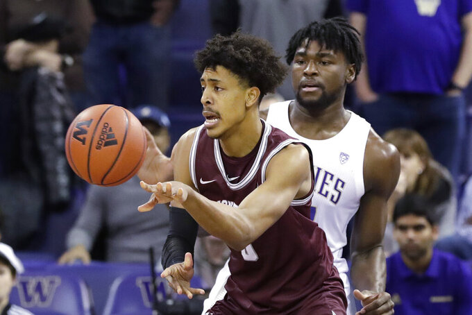Montana's Kyle Owens, left, passes the ball in front of Washington's Isaiah Stewart during the first half of an NCAA college basketball game Friday, Nov. 22, 2019, in Seattle. (AP Photo/Elaine Thompson)