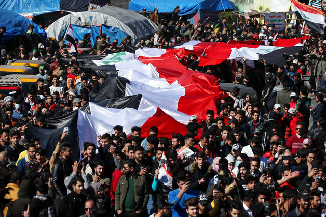 Anti-government protesters hold a huge Iraqi flag as they gather during a protest in Tahrir Square in Baghdad, Iraq, Sunday, Jan. 26, 2020. (AP Photo/Hadi Mizban)