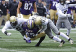 Washington tailback Sean McGrew (25) is tackled by Colorado's Davion Taylor, left, and Chris Miller-Slaughter (14) during the first half of an NCAA college football game, Saturday, Oct. 20, 2018, in Seattle. (AP Photo/Ted S. Warren)