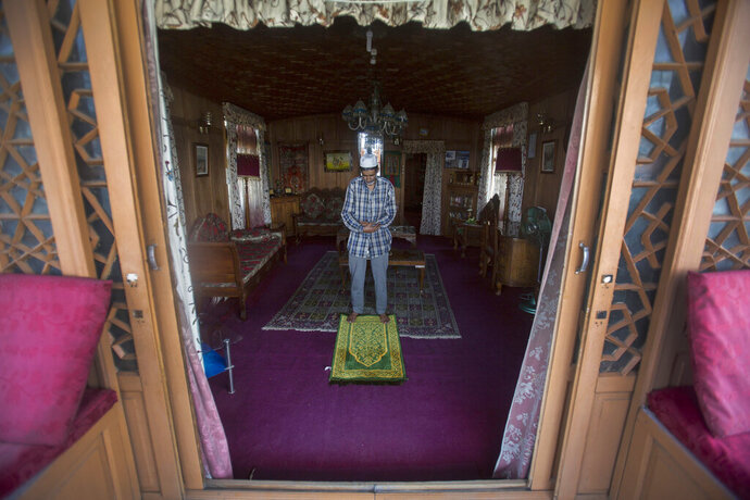 """Kashmiri houseboat owner Ghulam Qadir Ota offers prayers inside his houseboat during lockdown to stop the spread of the coronavirus at Nigeen Lake in Srinagar, Indian controlled Kashmir, July 24, 2020. """"We've not earned a single penny for a year now, all we have are these boats, We don't have any other means to earn,"""
