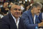 Claudio Tapia, president of Argentina's Soccer Federation, smiles as he poses for pictures during a press conference to announce the early implementation of a plan to professionalize women's soccer in Buenos Aires, Argentina, Saturday, March 16, 2019. Almost 90 years after men's soccer turned professional in Argentina, the women's game is still being played by amateur athletes who get little to no money for their work on the field. (AP Photo/Daniel Jayo)