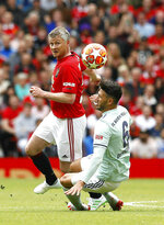 Manchester United Legends' Ole Gunnar Solskjaer, left, vies for the ball with Bayern Munich Legends' Martin Demichelis  during the legends soccer match at Old Trafford, in Manchester, Sunday May 26, 2019. (Martin Rickett/PA via AP)