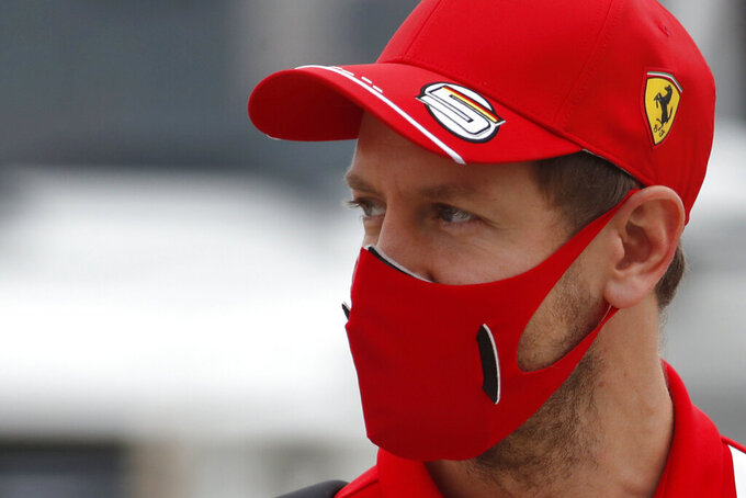 FILE - In this Friday, Nov. 27, 2020 file photo, Ferrari driver Sebastian Vettel of Germany arrives at the paddock ahead of the first free practice at the Formula One Bahrain International Circuit in Sakhir, Bahrain. The new season starts Sunday March 28, 2021 with the Bahrain Grand Prix and ends in December 2021 at Abu Dhabi. (Hamad Mohammed, Pool via AP, File)