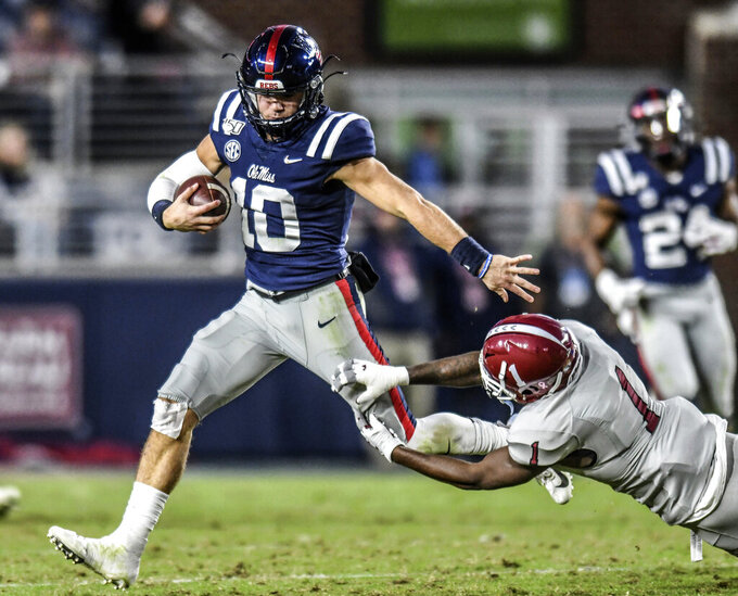 Mississippi quarterback John Rhys Plumlee (10) avoids an attempted tackle by New Mexico State defensive back Ray Buford Jr. (1) during an NCAA college football game in Oxford, Miss., Saturday, Nov. 9, 2019. (Bruce Newman/The Oxford Eagle via AP)