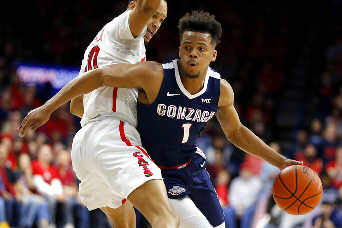 Gonzaga guard Admon Gilder (1) drives around Arizona guard Jemarl Baker Jr. in the first half of an NCAA college basketball game, Saturday, Dec. 14, 2019, in Tucson, Ariz. (AP Photo/Rick Scuteri)