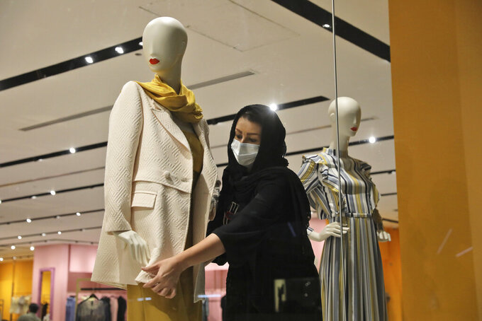 A shopkeeper adjusts a jacket on a mannequin at Iran Mall shopping center in Tehran, Iran, Wednesday, June 9, 2021. The West considers Iran's nuclear program and Mideast tensions as the most important issues facing Tehran, but those living in the Islamic Republic repeatedly point to the economy as the major issue facing it ahead of its June 18 presidential election. (AP Photo/Vahid Salemi)