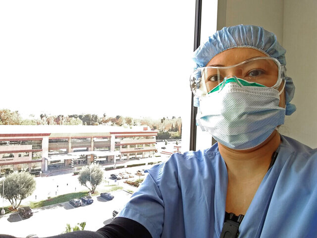 Nurse Nerissa Black takes a selfie wearing protective gear at work on Dec. 13, 2020 at Henry Mayo Newhall Hospital in Valencia, Calif. Black was already having a hard time tending to four COVID-19 patients who need constant heart monitoring. But because of staffing shortages affecting hospitals throughout California, her workload recently increased to six people infected with the coronavirus. Overwhelmed California nurses are now caring for more COVID-19 patients after the state began issuing waivers that allow hospitals to temporarily bypass strict nurse-to-patient ratios. Nurses say the new workload is pushing them to the brink of burnout and affecting patient care. (Nerissa Black via AP)