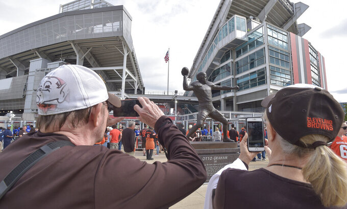 Cleveland Browns fans take a photo of the Otto Graham statue before an NFL football game between the Tennessee Titans and the Cleveland Browns, Sunday, Sept. 8, 2019, in Cleveland. The team unveiled a bronze statue on Saturday outside FirstEnergy Stadium of the late Hall of Fame quarterback, who led Cleveland to 10 championship games in 10 seasons. Graham, who died in 2003, has long been considered one of the best QBs in professional history. However, he isn't always mentioned among the game's elite players like Joe Montana, Tom Brady, Brett Favre or Johnny Unitas. (AP Photo/David Richard)