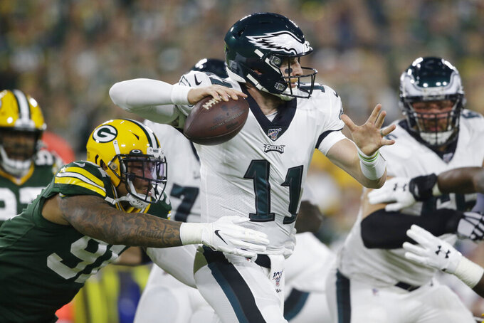 Philadelphia Eagles quarterback Carson Wentz is pressured by the defense of Green Bay Packers outside linebacker Preston Smith during the first half of an NFL football game Thursday, Sept. 26, 2019, in Green Bay, Wis. (AP Photo/Jeffrey Phelps)