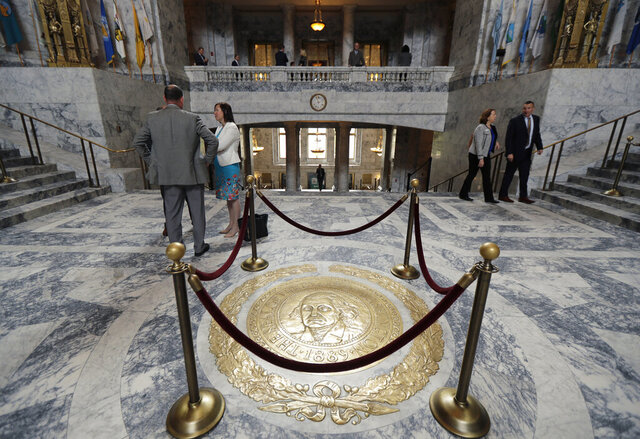 FILE - This April 22, 2019 file photo shows the Washington state seal protected by ropes in the rotunda of the Legislative Building at the Capitol in Olympia, Wash. The 60-day legislative session in Washington state begins Monday, Jan. 13, 2020, with lawmakers set to make adjustments to the state budget as well as tackle several policy issues, including how to address homelessness in the state. (AP Photo/Ted S. Warren, File)