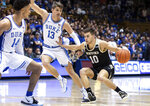 Wofford's Nathan Hoover (10) handles the ball as Duke's Joey Baker (13) and Jordan Goldwire (14) defend during the first half of an NCAA college basketball game in Durham, N.C., Thursday, Dec. 19, 2019. (AP Photo/Ben McKeown)