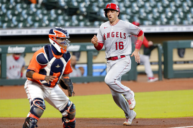 Los Angeles Angels' Jason Castro (16) scores as Houston Astros catcher Martin Maldonado, left, waits for the ball during the fifth inning of the first game of a doubleheader baseball game Tuesday, Aug. 25, 2020, in Houston. (AP Photo/Michael Wyke)