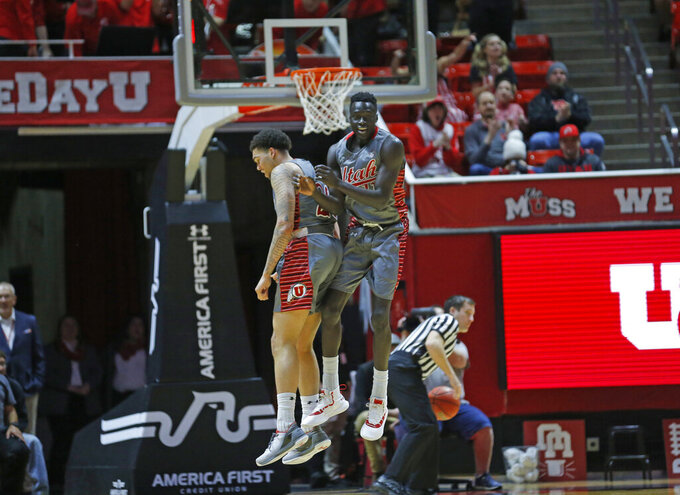Utah forward Both Gach, right, celebrates with teammate Timmy Allen, right, after scoring against Colorado during the first half of an NCAA college basketball game Sunday, Jan. 20, 2019, in Salt lake City. (AP Photo/Rick Bowmer)