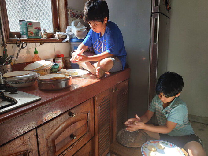 """FILE - In this Sunday, April 19, 2020 photo provided by Anil Sanweria, his sons, Uddhav Pratap, 8, left, and Advait Vallabh, 9, help in the kitchen during a nationwide COVID-19 coronavirus lockdown. The brothers believe the lockdown should continue for a year. """"They shouldn't reopen till the time there are zero cases left,"""" the younger Uddhav Pratap says. (Anil Sanweria via AP, File)"""