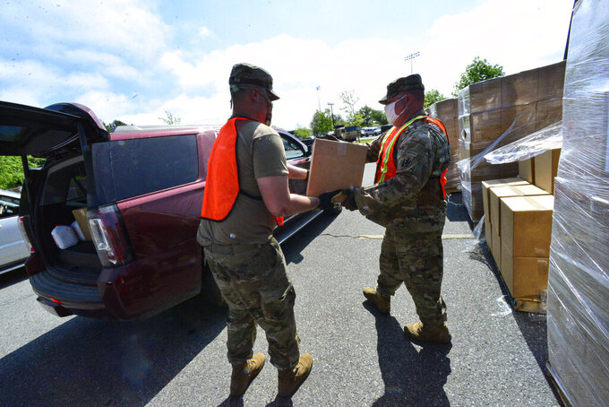 Vermont National Guard Pvt. Culann Gage and Sgt. Scott Gordon help load food boxes into vehicles at a Farmers to Families Food Box Distribution site at Brattleboro Union High School in Brattleboro, Vt., on Wednesday, May 27, 2020. (Kristopher Radder/The Brattleboro Reformer via AP)