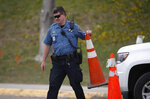 A Jefferson County, Colo. Schools officer blocks a driveway with a pylon outside Columbine High School as students leave late Tuesday, April 16, 2019, in Littleton, Colo. Following a lockdown at Columbine High School and other Denver area schools, authorities say they are looking for a woman suspected of making threats. (AP Photo/David Zalubowski)