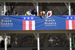 Workers put up bunting on a press riser for the upcoming inauguration of President-Elect Biden and Vice President-Elect Kamala Harris, on Pennsylvania Avenue in front of the White House, Thursday, Jan. 14, 2021, in Washington. (AP Photo/Gerald Herbert)