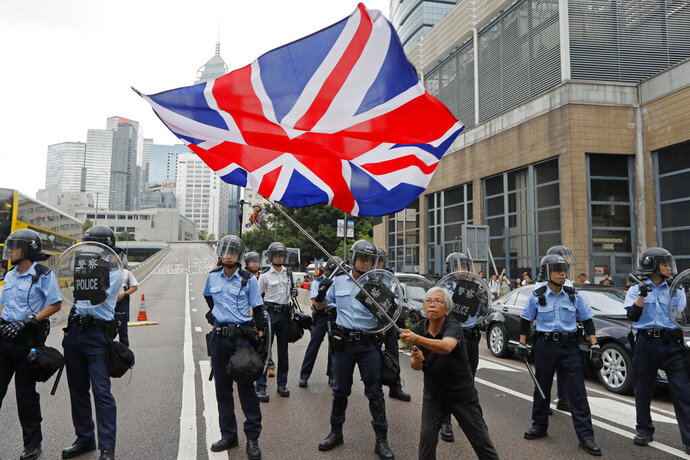 In this Wednesday, June 12, 2019, photo, a woman waves a British flag as policemen in anti-riot gear stand guard against the protesters on a closed-off road near the Legislative Council in Hong Kong. China promised that for 50 years after Britain gave up control of its last colony in 1997, this shimmering financial enclave would get to keep freedoms absent in the communist-ruled mainland that many here don't want to live without. (AP Photo/Kin Cheung)
