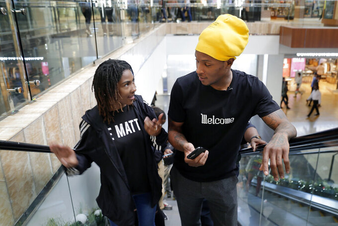 Miracle Washington-Tribble, left, and Houston Texans' De'Andre Hopkins, right, chat on an escalator as they shop for Christmas clothes Monday, Dec. 16, 2019, at Galleria Mall in Houston. Washington-Tribble and Jadon Cofield are beneficiaries of Eight Million Stories, a Houston program which helps 14-18-year-olds who have either quit or been kicked out of school continue their education, find employment and receive emotional support. (AP Photo/Michael Wyke)