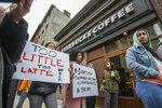 Protesters gather outside of a  Starbucks in Philadelphia, Sunday, April 15, 2018, where two black men were arrested Thursday after employees called police to say the men were trespassing. The arrest prompted accusations of racism on social media. Starbucks CEO Kevin Johnson posted a lengthy statement Saturday night, calling the situation