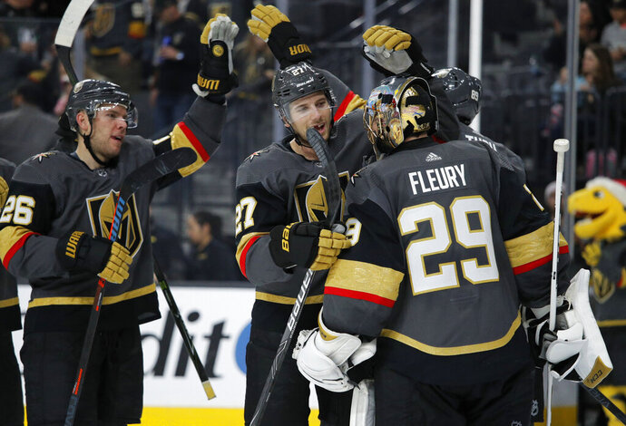 Vegas Golden Knights goaltender Marc-Andre Fleury, right, celebrates with defenseman Shea Theodore (27) and other teammates after defeating the Vancouver Canucks in an NHL hockey game Sunday, Dec. 15, 2019, in Las Vegas. (AP Photo/John Locher)