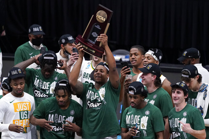 Baylor players celebrate with the trophy after an Elite 8 game against Arkansas in the NCAA men's college basketball tournament at Lucas Oil Stadium, Tuesday, March 30, 2021, in Indianapolis. Baylor won 81-72. (AP Photo/Darron Cummings)