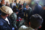 Relatives stand around the dead body of a boy who was killed by a mortar shell attack in Kabul, Afghanistan, Saturday, Nov. 21, 2020. Mortar shells slammed into different parts of the Afghan capital on Saturday. (AP Photo/Rahmat Gul)