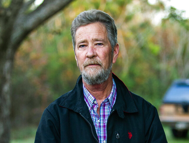 FILE - In this Dec. 5, 2018, file photo, Leslie McCrae Dowless Jr. poses for a portrait outside of his home in Bladenboro, N.C. Dowless, a political operative already accused in state court of absentee ballot fraud during a 2018 North Carolina congressional election, now faces federal charges of fraudulently receiving Social Security benefits while getting paid for political work, prosecutors said Tuesday, April 21, 2020. (Travis Long/The News & Observer via AP)