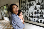 FILE - In this Feb. 12, 2009, file photo, a local woman holds her baby as she stands next to portraits of former prisoners on display at a the notorious former Khmer Rouge prison, S-21, now the Tuol Sleng genocide museum, in Phnom Penh, Cambodia. The Khmer Rouge's chief jailer, who admitted overseeing the torture and killings of as many as 16,000 Cambodians while running the regime's most notorious prison, died at a hospital in Cambodia early Wednesday morning, Sept. 2, 2020. Kaing Guek Eav, known as Duch, was 77 and had been serving a life prison term for war crimes and crimes against humanity. (AP Photo/Heng Sinith, File)