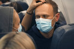 Alexei Navalny and his wife Yulia sit on the plane on a flight to Moscow, at the Airport Berlin Brandenburg (BER) in Schoenefeld, near Berlin, Germany, Sunday, Jan. 17, 2021. Leading Kremlin critic Alexei Navalny flew home to Russia on Sunday after recovering in Germany from his poisoning in August with a nerve agent. (AP Photo/Mstyslav Chernov)