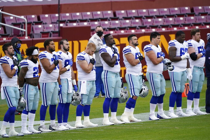 Members of the Dallas Cowboys on the sidelines during the national anthem before the start of the first half of an NFL football game against Washington Football Team, Sunday, Oct. 25, 2020, in Landover, Md. (AP Photo/Susan Walsh)