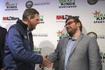 New Hampshire Gov. Chris Sununu, left, shakes hands with DraftKings co-founder Matt Kalish smiles after placing the first legal sports wagering bet on his mobile phone for the New England Patriots to win the Super Bowl at a sports bar in Manchester, N.H., Monday, Dec. 30, 2019. New Hampshire, who partnered with DraftKings, is the second New England state to approve sports wagering. (AP Photo/Charles Krupa)