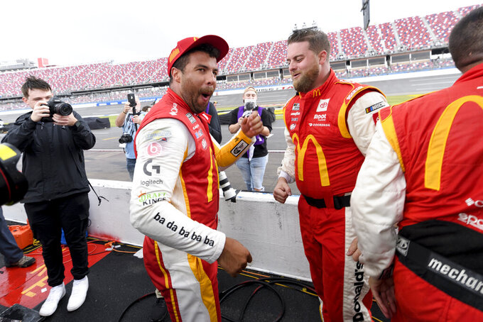 Bubba Wallace, center, celebrates after being pronounced the winner while waiting out a rain delay before which he was the leader in a NASCAR Cup series auto race Monday, Oct. 4, 2021, in Talladega, Ala. (AP Photo/John Amis)