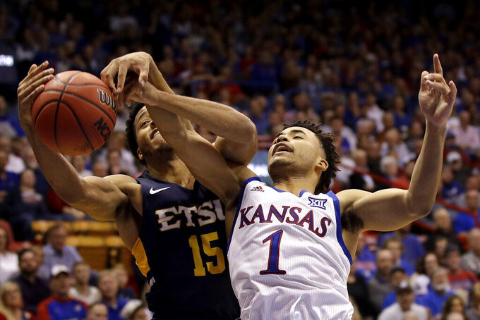 East Tennessee State guard Isaiah Tisdale (15) and Kansas guard Devon Dotson (1) battle for a rebound during the second half of an NCAA college basketball game Tuesday, Nov. 19, 2019, in Lawrence, Kan. Kansas won 75-63. (AP Photo/Charlie Riedel)