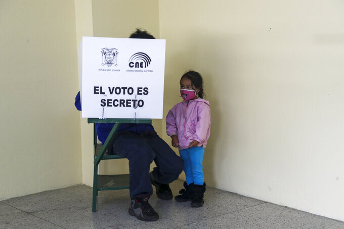 A voter, accompanied by his daughter, marks his ballot during a runoff presidential election in Quito, Ecuador, Sunday, April 11, 2021. Ecuadorians are voting, amid the COVID-19 pandemic, to choose between Andres Arauz, from the Union of Hope coalition, an economist protégé of former President Rafael Correa, and former banker Guillermo Lasso, of Creating Opportunities party, or CREO.  (AP Photo/Dolores Ochoa)