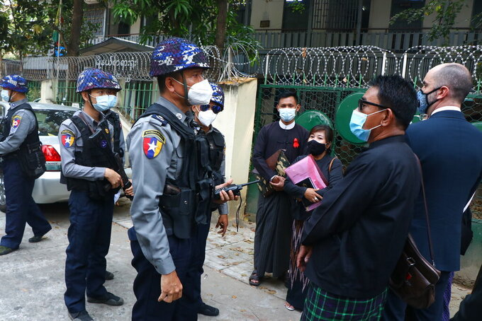 Myanmar police talk to people gathering outside the Kamayut court in Yangon, Myanmar Friday, March 12, 2021. A court in Myanmar is scheduled to hold a hearing on Friday for an Associated Press journalist detained while covering demonstrations against the military's seizure of power last month. He is facing a charge that could send him to prison for three years. (AP Photo)
