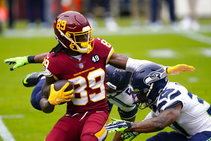 Washington Football Team wide receiver Cam Sims (89) is tackled by Seattle Seahawks free safety Quandre Diggs (37) and outside linebacker K.J. Wright (50) during the first half of an NFL football game, Sunday, Dec. 20, 2020, in Landover, Md. (AP Photo/Mark Tenally)