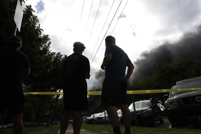 Bystanders watch black smoke billowing from a house fire after a shooting and domestic incident at a residence on Hibiscus Road near Diamond Head on Sunday, Jan. 19, 2020, in Honolulu. Witnesses say at least two Honolulu police officers were shot and two civilians were injured. Moments after the shooting, the house was set on fire, possibly by the suspect. (Jamm Aquino/Honolulu Star-Advertiser via AP)