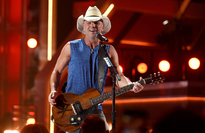 "FILE - In this April 15, 2018, file photo, Kenny Chesney performs ""Get Along"" at the 53rd annual Academy of Country Music Awards at the MGM Grand Garden Arena on Sunday, in Las Vegas. Through his song ""Boys of Fall,"" Kenny Chesney has a direct connection to this Super Bowl. The song has become something of an anthem for high school football, celebrating the teamwork and dedication it takes to play the sport _ really on any level. It was written by Pro Football Hall of Famer Bobby Beathard's son Casey, who has penned several hits for the country superstar. Beathard's son, C.J., is a backup quarterback for the 49ers.(Photo by Chris Pizzello/Invision/AP, File)"