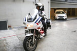 A police motorcycle escorts a hearse, right, carrying the body of former Zimbabwe President Robert Mugabe leaving the Singapore Casket Funeral Parlour for the airport in Singapore Wednesday, Sept. 11, 2019. Mugabe died Friday, Sept. 6 at a hospital in Singapore at age 95. (AP Photo/Danial Hakim)