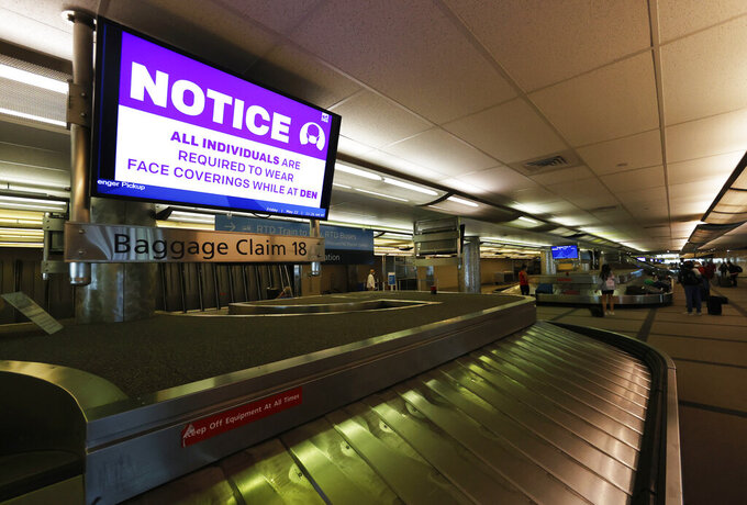 FILE - In this May 22, 2020 file photo, a message to wear a face mask flashes across a television monitor as travelers retrieve their bags off a carousel at Denver International Airport in Denver. Airlines are requiring passengers to wear masks, but recent incidents involving young children have put the carriers on the spot for how they enforce rules on face coverings. (AP Photo/David Zalubowski, File)