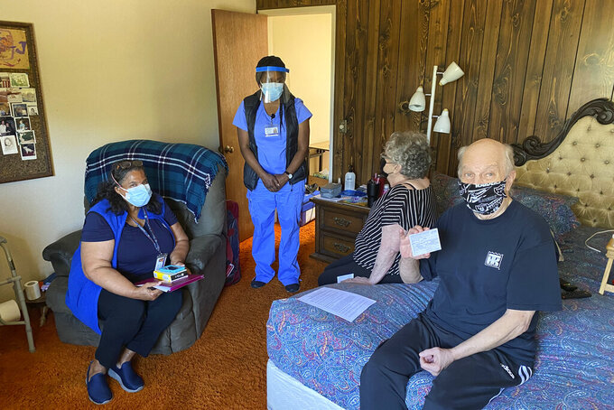 John McFarland, 70, shows his vaccination card after receiving the COVID-19 vaccine inside his bedroom in Hayward, Calif., May 6, 2021. Alameda County nurses Patricia Calloway, left, and Devette Laflore chat with his wife, Patti Amaral, 73, while they waited to make sure there were no vaccine side effects.  (AP Photo/Terry Chea)