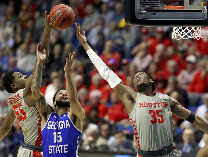 Georgia State's D'Marcus Simonds (15) reaches for a rebound along with Houston's Brison Gresham (55) and DeJon Jarreau (13) during the first half of a first round men's college basketball game in the NCAA Tournament Friday, March 22, 2019, in Tulsa, Okla. (AP Photo/Jeff Roberson)
