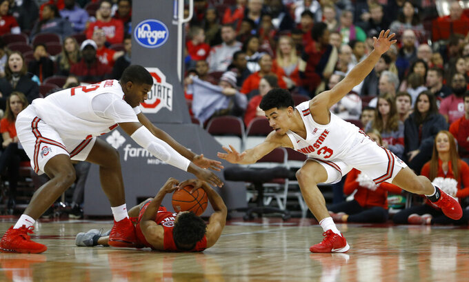 Ohio State's E.J. Liddell, left, and D.J. Carton, right, try to grab a loose ball from Southeast Missouri State's DQ Nicholas during the second half of an NCAA college basketball game Tuesday, Dec. 17, 2019, in Columbus, Ohio. Ohio State defeated Southeast Missouri State 80-48. (AP Photo/Jay LaPrete)