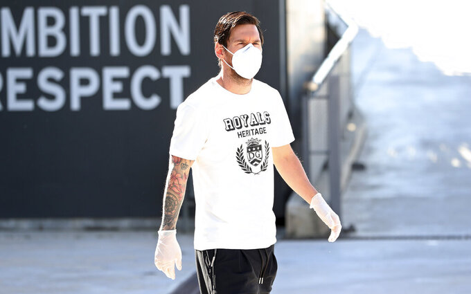 In this photo provided by FC Barcelona, Lionel Messi walks wearing a protective face mask at the club's training ground in Barcelona, Spain, on Wednesday May 6, 2020.  Soccer players in Spain returned to their team's training camps Wednesday for the first time since the country entered a lockdown nearly two months ago because of the coronavirus pandemic. Players for Barcelona, Real Madrid, Atlético Madrid and other clubs started preparing for the return to training this week, and they were all expected to be tested for COVID-19 and should be cleared to practice once the results are back. (Miguel Ruiz / FC Barcelona via AP)