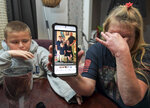 Darra Ann Morales, right, shows a photo of her son Chaz Morales and his family on her phone, as Chaz Jr., 10, comforts his grandmother at their home in Slidell, La., Wednesday, April 14, 2021. Darra Ann Morales is the mother and Chaz Jr. is the son of Chaz Morales, who is one of the crew members missing from the capsized vessel Seacor Power that departed from Port Fourchon when severe weather struck Tuesday. (Max Becherer/The Times-Picayune/The New Orleans Advocate via AP)