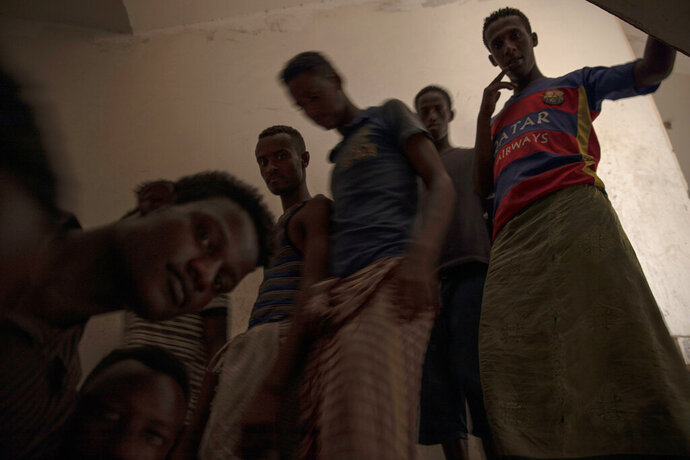 In this July 21, 2019 photo, Ethiopian migrants run down stairs in the
