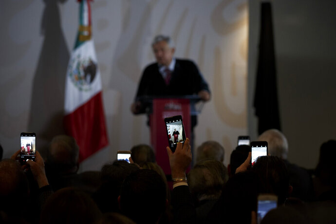 People use their smartphones to capture Mexico's President Andres Manuel Lopez Obrador as he gives a presentation on his new economic program for the northern border zone, in Tijuana, Mexico, Sunday, Jan. 6, 2019. (AP Photo/Daniel Ochoa de Olza)